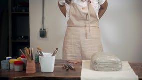 A mulher está pondo sobre um avental em sua oficina do artesanato, estando perto da tabela, vídeos de arquivo