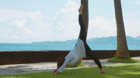 A mulher está praticando a ioga, exercício na pose da montanha e está esticando o pé acima, na praia, no fundo bonito e nos sons  vídeos de arquivo