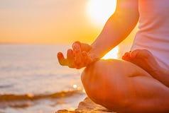 A mulher está praticando o assento da ioga na pose de Lotus no nascer do sol Silhueta da mulher que medita no por do sol na praia fotos de stock