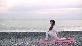 A mulher está relaxando em asanas da ioga na costa de mar do seixo no tempo de manhã video estoque
