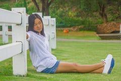 A mulher está relaxando no jardim exterior Ela que senta-se na grama verde imagens de stock royalty free