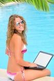 A mulher está sentando-se com portátil imagem de stock