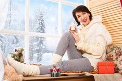 A mulher está sentando-se em um peitoril da janela e está mostrando-se um anjo da cookie Vista bonita fora da janela - dia ensola fotografia de stock
