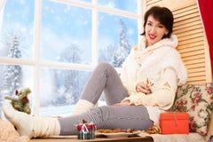 A mulher está sentando-se em um peitoril da janela e está mostrando-se um anjo da cookie Vista bonita fora da janela - dia ensola imagem de stock royalty free