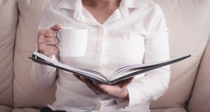 A mulher está sentando-se em um sofá e está lendo-se um livro ao guardar um co imagens de stock royalty free