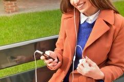 A mulher está sentando-se, guarda o telefone em suas mãos e escuta a música Imagens de Stock Royalty Free
