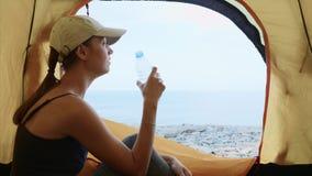 A mulher está sentando-se na barraca de acampamento, na água potável da garrafa e em olhar o mar filme