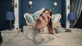 A mulher está sentando-se na cama video estoque
