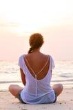 A mulher está sentando-se na praia no nascer do sol foto de stock