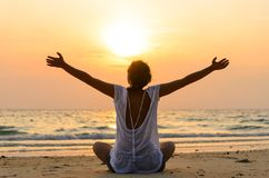 a mulher está sentando-se na praia no nascer do sol imagens de stock