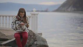 A mulher está sentando-se no cais situado no litoral do lago que trabalha com PC da tabuleta video estoque