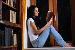 A mulher está sentando-se no indicador e na leitura imagens de stock