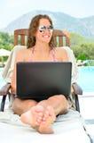 A mulher está sentando-se no poolside com portátil foto de stock