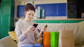 A mulher está sentando-se no sofá com sacos de compras e na compra que usa em linha um cartão de crédito, um telefone celular e u filme