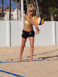 A mulher está servindo o voleibol de praia Foto de Stock Royalty Free