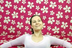 A mulher está sonhando acordado na frente do sofá cor-de-rosa Imagens de Stock Royalty Free