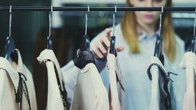 A mulher está tocando em ganchos com as blusas na sala de exposições vídeos de arquivo
