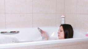 A mulher está tomando um banho com espuma Derrama sua água do corpo do chuveiro