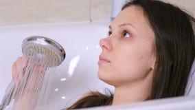 A mulher está tomando um banho Derrama sua água do corpo do chuveiro Face do Close-up filme