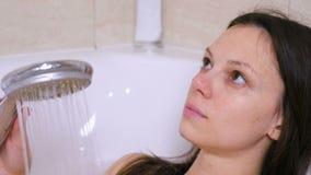 A mulher está tomando um banho Derrama sua água do corpo do chuveiro Face do Close-up vídeos de arquivo