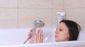 A mulher está tomando um banho Relaxe após um dia mau Toque em uma água com mão