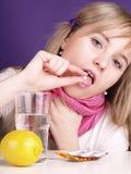 A mulher está tomando um comprimido Imagens de Stock