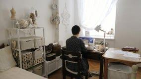 A mulher está trabalhando na máquina de costura Vista traseira vídeos de arquivo
