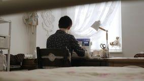 A mulher está trabalhando na máquina de costura Vista traseira filme
