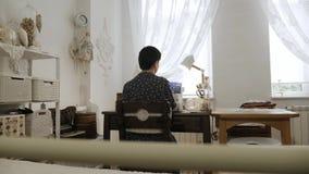 A mulher está trabalhando na máquina de costura Vista traseira video estoque