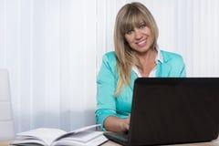 A mulher está trabalhando no caderno foto de stock royalty free
