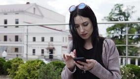 A mulher está usando o smartphone filme
