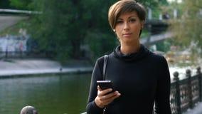 A mulher está usando um smartphone em exterior filme