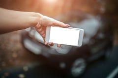 A mulher está usando um smartphone Menina que toma imagens dos carros fotografia de stock