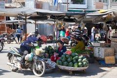 A mulher está vendendo maçãs de estrela e melancias no mercado molhado Imagem de Stock