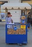 A mulher está vendendo prezels na rua de Krakow, Polônia Imagem de Stock