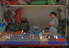 A mulher está vendendo sementes, porcas e grões no Fotografia de Stock Royalty Free