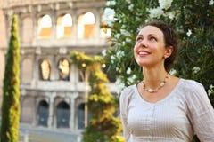 A mulher está Colosseum próximo e olha acima Imagens de Stock Royalty Free