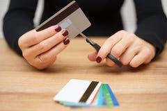 A mulher está destruindo cartões de crédito devido ao débito grande Imagem de Stock