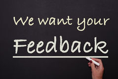 A mulher está escrevendo no quadro-negro que nós queremos seu feedback Imagens de Stock Royalty Free