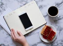 A mulher est? planejando o dia, caf?, waffles, fundo de m?rmore, smartphone fotografia de stock