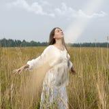 A mulher está relaxando com nascer do sol Foto de Stock
