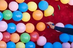 Mulher estalando balões coloridos com um dardo foto de stock
