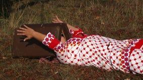 Mulher estranha no vestido pontilhado branco que encontra-se no prado video estoque