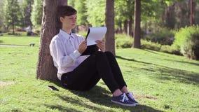 Mulher, estudante que faz suas tarefas no parque vídeos de arquivo