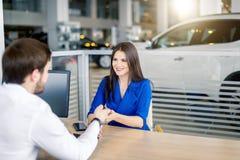 Mulher europeia atrativa que recebe chaves do carro do agente de vendas do carro imagem de stock royalty free