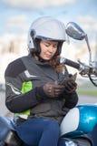 Mulher europeia de Motorbiker no capacete de impacto aberto branco da cara que disca um número em seu smartphone ao sentar-se no  imagem de stock