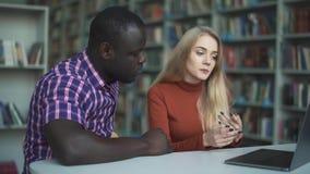 Mulher europeia e homem afro-americano que estudam na biblioteca com portátil filme