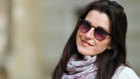 Mulher europeia moreno bonita que levanta nos óculos de sol modernos à moda que sorriem e que olham a câmera filme