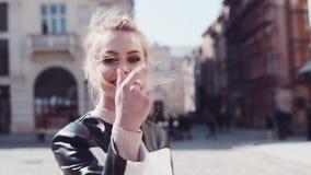 A mulher europeia nova atrativa com um sorriso bonito anda abaixo do centro da cidade, gerencie para a câmera, dá um sorriso bril vídeos de arquivo