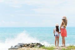 A mulher europeia nova e sua irmã pequena do filha ou a mais nova são ficando e guardando as mãos de se na costa do SE azul Fotografia de Stock